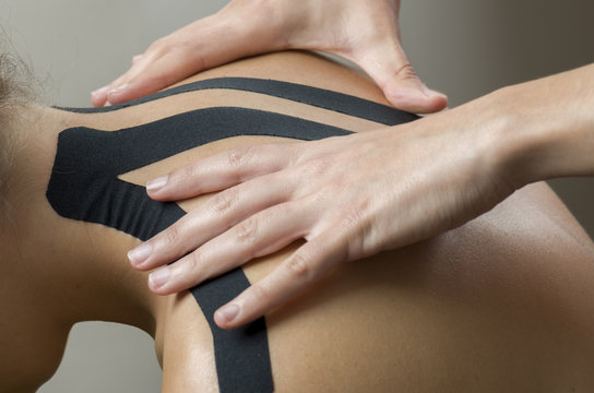 Physiotherapist putting on black kinesio tape on woman patients