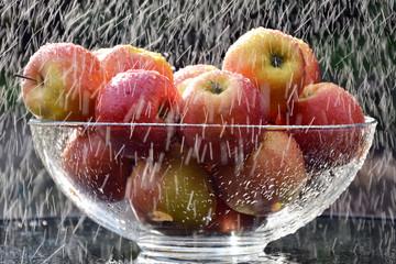 szklana misa z czerwonymi jabłkami w strugach deszczu