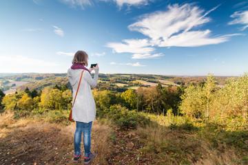 junge frau fotografiert landschaft mit dem handy