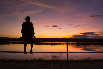 Obraz silhouette woman sitting alone on fence look at the sky - fototapety do salonu