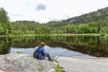 Alone young girl sitting near by beautiful blue lake