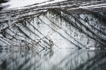 Layers in gravelly glacier cliff reflected in a small glacial lake, jasper national park;Alberta, canada