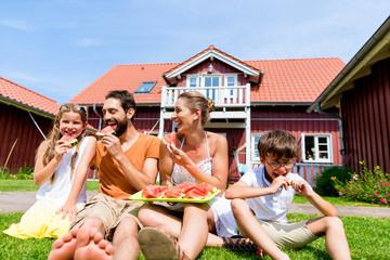 Familie sitzt vor Haus und isst Wassermelone im Garten