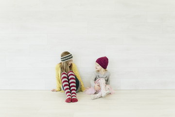 Two young girls sit and talk against a white wall
