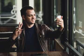 Young man taking a selfie in coffee shop