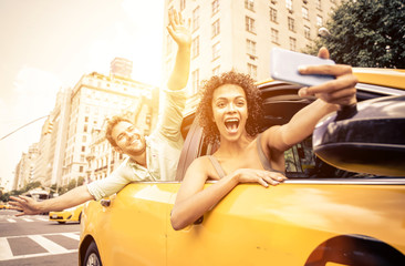 Happy couple driving in New york on a yellow cab and taking self