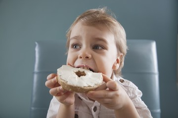 Toddler Biting A Bagel With Cream Cheese; Jordan, Ontario, Canada