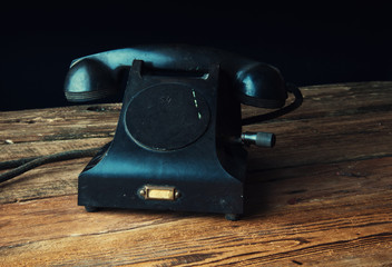 Old-fashioned landline telephone on dark wooden background
