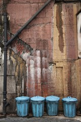 Four Garbage Cans In A Row Against A Dirty Wall In An Alley; Tokyo, Japan