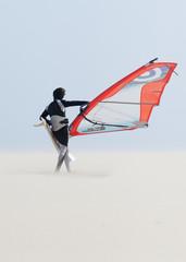 A Windsurfer Walks On The Sand Of Punta Paloma Beach With His Board; Tarifa, Cadiz, Andalusia, Spain