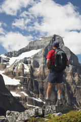 Male Hiker With A Backpack On Cliff Lookout Overlooking A Mountain Face With Snow; Lake Louise, Alberta, Canada