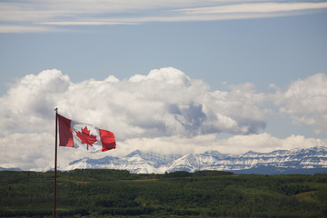 Canadian Flag Blowing In The Wind With Snowy Mountains In The Distance And Clouds With Blue Sky; Alberta, Canada