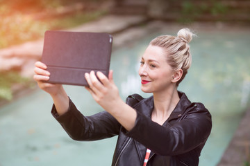 beautiful and stylish woman taking a selfie by the pool, using her tablet. graded in instagram style