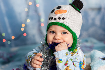 baby in a Christmas snowman holding holiday decorations tinsel,