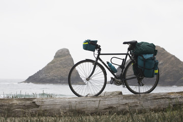 Touring Bicycle With Full Bags On A Beach With Rock Formation In The Ocean In The Background; Heceta Head, Oregon, United States of America