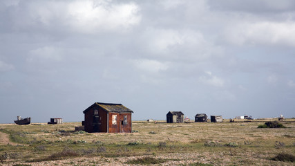 Numerous small wooden sheds and a boat scattered across a field; Dungeness, Sussex, England