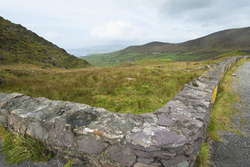 A stone wall between a grass field and road;Ireland