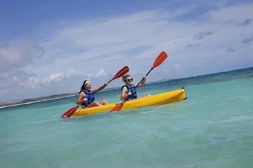 Two Women In Lifejackets Paddling In A Yellow Boat; Punta Cana, La Altagracia, Dominican Republic