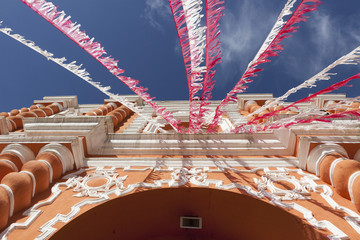 White And Red Streamers Blowing In The Wind Strung Above A Building's Doorway; Guatemala City, Guatemala