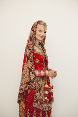 Portrait Of A Bride With Blond Hair Wearing A Red And Gold Sari; Ludhiana, Punjab, India