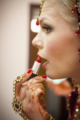A Woman With Mehndi Jewelry On Her Hands And Applies Lipstick; Ludhiana, Punjab, India