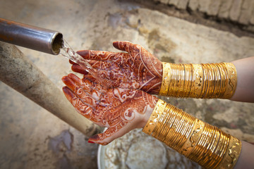 Water Pouring Out Of A Spout Into Palms Covered With Mehndi; Ludhiana, Punjab, India