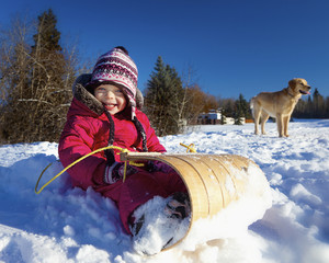 A Young Girl Sits On A Toboggan In The Snow With A Dog In The Background; Spruce Grove, Alberta, Canada