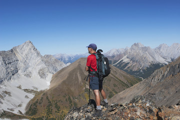 Male Hiker On Top Of Mountain Ridge Overlooking Valley And Mountains In The Distance With Blue Sky; Alberta, Canada