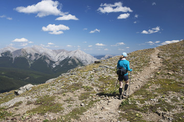 Female Hiker With Hiking Poles Along Ridge Trail With Mountians And Valley In The Distance And Blue Sky And Clouds; Alberta, Canada