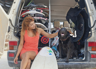 A Woman Sits In The Back Of A Vehicle With A Surfboard And Petting A Dog; Tarifa, Cadiz, Andalusia, Spain