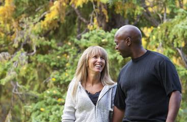 Interracial Couple Walking In A Park In Autumn; Edmonton, Alberta, Canada