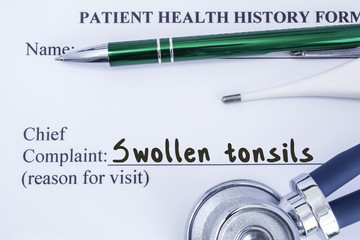 Complaint of swollen tonsils. Paper health history form, which is written on patient's chief complaint of swollen tonsils, surrounded by a stethoscope, electronic thermometer and green ball-point pen