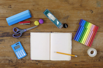 Overhead view of a desk with school homework objects including waiting pad