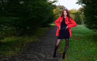 The girl with long hair in red coat standing on the road in the Park