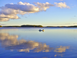 Rowing boat on beautiful calm lake with blue sky. Outdoor poster.