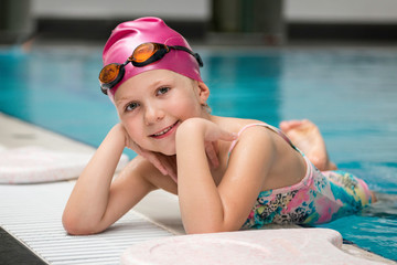 Little girl posing on the swimming pool edge
