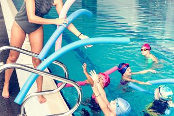 Swimming school. Children having fun with water noodles