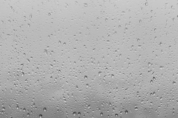 Photo of raindrops on window glasses surface with cloudy background.