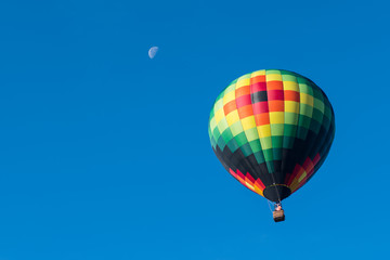This is a photo of a beautiful hot air balloon slowly sailing through a calm blue sky with a moon in the background.