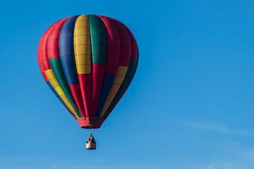 This is a photo of a beautiful hot air balloon slowly sailing through a calm blue sky.