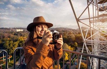 Woman with camera ride Ferris wheel