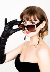 Beauty retro female model with professional makeup in a long leather gloves, holding over size sunglasses
