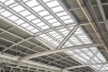 Gray and white metal roof structure in sunny day.