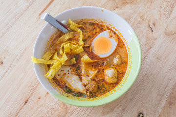 Spicy Thai Tomyum noodle with pork, vegetable, egg and balls.
