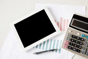 Blank digital tablet on stock and finance graph papers on desk with calculator and pen- with copy space