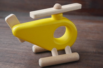 An yellow wooden helicopter toy for children