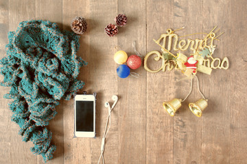 Flat lay of winter scraft, Christmas decoration items and smartp