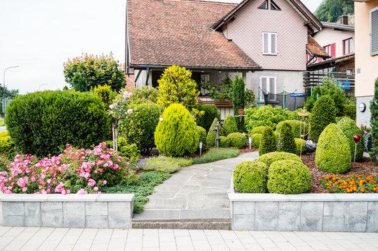 House front yard with flowers and trees in Vaduz, Lichtenstein