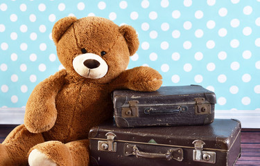 Teddy bear with old suitcases, sitting on a wooden floor with wooden background and copy space. Travel scene.