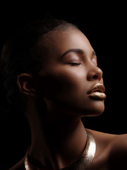Fototapete - Fashion studio portrait of an extraordinary beautiful nude african american woman with perfect smooth glowing mulatto skin, make up, full golden lips, shaved haircut and gold necklace, profile